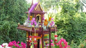 Wooden miniature guardian spirit house. Small buddhist temple shrine, colorful flower garlands. San phra phum erected to. Bring fortune. Traditional respect stock video footage