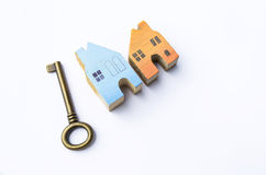 Wooden miniature house with metal antique key on white background Stock Photography