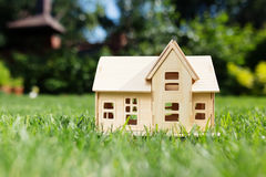 Wooden model of house on grass Royalty Free Stock Images
