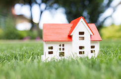 Wooden model of house on grass Stock Photo