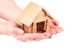 Wooden model house in hands Royalty Free Stock Images