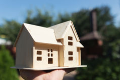 Wooden model of house in hands Stock Photography