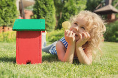 Wooden model of house and little blonde girl Stock Photography