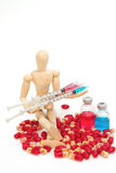 Wooden model  with medicine vials, syringe and pills Stock Photo
