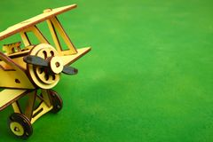 Wooden old airplane. A wooden model of an old airplane  on a green background. Close-up Royalty Free Stock Images
