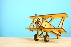 Wooden old airplane. A wooden model of an old airplane  on a table on a blue background Stock Images