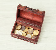 Wooden money chest filled with coins Royalty Free Stock Image