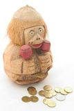 Wooden Monkey Bank and Coins. A hand carved wooden bank in the shape of a monkey with glasses, maracas and gold coins Stock Photos