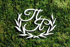 The wooden monogram is the white initials of the newlyweds on th. E background of green moss. Wedding decor, decoration of a banquet table Royalty Free Stock Photo