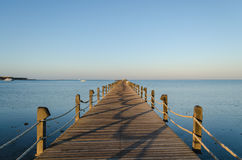 Wooden moorage going away to the sea. A wooden pier going away to the sea in the rays of a sunset sun, Hurghada, Egypt, January 2016 Stock Photos