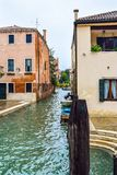 Wooden mooring poles and docked boats along sides of a waterway/water canal in Venice, Italy stock photography