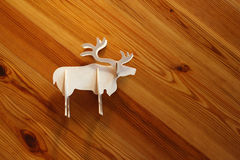 Wooden Moose ornament. European 3 dimensional moose figurine cut out of lighter wood on a darker pine wooden background stock image