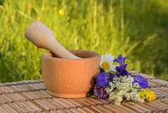 Wooden mortar with a bouquet of summer wildflowers Royalty Free Stock Photography