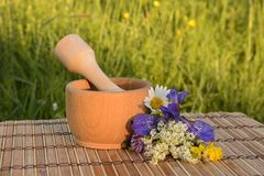 Wooden mortar with a bouquet of summer wildflowers Stock Photo