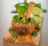 Wooden mortar, mint and limes Royalty Free Stock Photo