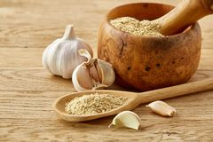 Wooden mortar and pestle with garlic and grind spices on rustic table, close-up, selective focus. Beautiful kitchen still life wooden mortar full of grind stock photography