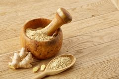 Wooden mortar and pestle with ginger and grind spices on rustic table, close-up, selective focus. Beautiful kitchen still life wooden mortar full of grind stock images