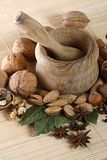 Wooden mortar and pestle with spices and nuts Stock Photo