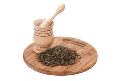 Wooden mortar and pile of green tea on the wooden board Royalty Free Stock Photo