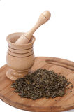 Wooden mortar and pile of green tea on the wooden board Royalty Free Stock Photography