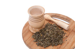Wooden mortar and pile of green tea on the wooden board Stock Photos