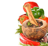 Wooden mortar with spices and vegetables Royalty Free Stock Photography