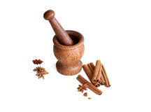 Wooden mortar, star anise, cinnamon. On a white background Royalty Free Stock Photo