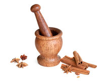 Wooden mortar, star anise, cinnamon. On a white background Royalty Free Stock Photography