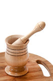 Wooden mortar on the wooden kitchen board Stock Photos