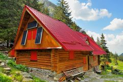 Wooden mountain chalet with solar panels Royalty Free Stock Photo