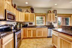 Wooden mountain home kitchen with golden  tile floor. Royalty Free Stock Photos