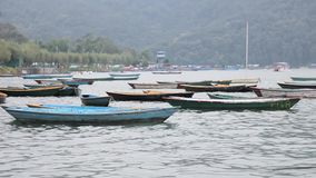 Wooden multi-colored empty boats anchored on a lake at the shore against the background of a green mountain. A wooden multi-colored empty boats anchored on a stock footage