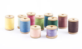 Wooden multicolored thread coils on white. Background Stock Photos