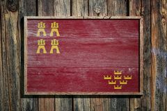 Wooden Murcia Community flag. 3d rendering of a Murcia Community flag on a wooden frame and a wood wall Stock Photos