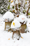 Wooden mushroom decoration during snowfall in winter garden. Stock Images
