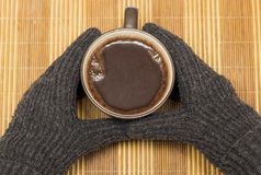 On a wooden napkin there is a mug with cocoa, which is held by hands in winter gloves Stock Photo