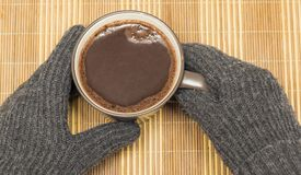 On a wooden napkin there is a mug with cocoa, which is held by hands in winter gloves Stock Photos