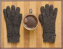 On a wooden napkin there is a mug of cocoa and winter gloves. On a wooden napkin there is a mug of cocoa and winter gloves Stock Image