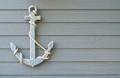Wooden nautical anchor on wood wall Stock Photos