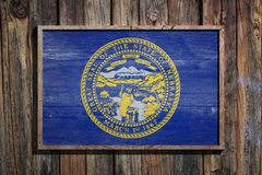 Wooden Nebraska flag. 3d rendering of a Nebraska State USA flag on a wooden frame and a wood wall Stock Photography