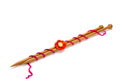 Wooden needles. And crocheted orange flower  on white background Stock Images