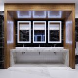 Wooden niche with mirrors, lights and sinks on the wall of black marble in a public toilet. 3d rendering stock illustration