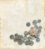 Wooden Nickel and Coins on a Grunge Background Stock Photos