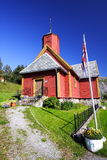 Wooden Norwegian church. Exterior of traditional red wooden Norwegian church in countryside with flag in foreground Stock Photography