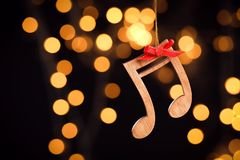 Wooden Notes Against Blurred Lights. Christmas Music Stock Photography