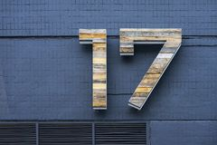 Wooden number seventeen on blue brick wall with ventilation grilles Royalty Free Stock Images