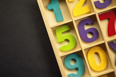 Wooden Numbers. Colorful wooden numbers in wooden container, empty left side royalty free stock image
