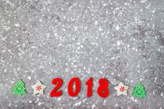 Wooden numbers forming the number 2018, For the new year and snow on a gray concrete background. Stock Image