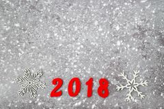 Wooden numbers forming the number 2018, For the new year and snow on a gray concrete background royalty free stock photo