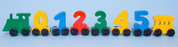 wooden numbers 0,1,2,3,4,5 letters train cars alphabet . Bright colors of red yellow green on a white background. Early mathematic royalty free stock photo